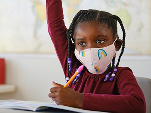 A Student Wearing A COVID Mask And Raising Her Hand